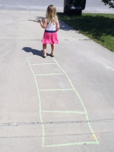 Aviana, age 2, gets some outdoor activity by jumping in boxes made with sidewalk chalk.